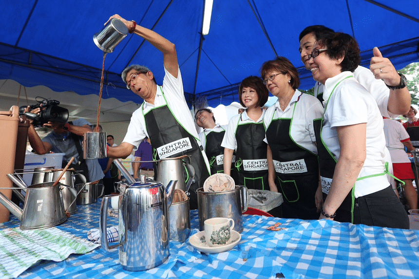 Minister for Communications and Information Yaacob Ibrahim trying his hand at making teh tarik as his Jalan Besar GRC team members (from left) Lily Neo, Denise Phua and Heng Chee How look on.