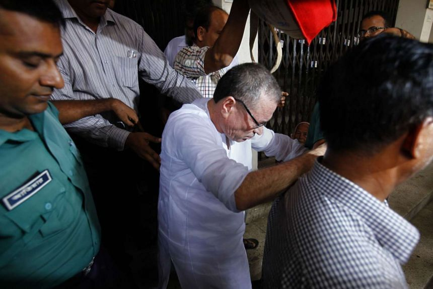 A director of now closed BCI Bangladesh, Shahjahan Sarker (centre) appears in court in Dhaka on Aug 17. A Bangladesh court sentenced six senior employees to jail for making toxic paracetamol syrup that doctors say killed hundreds of children in the 1