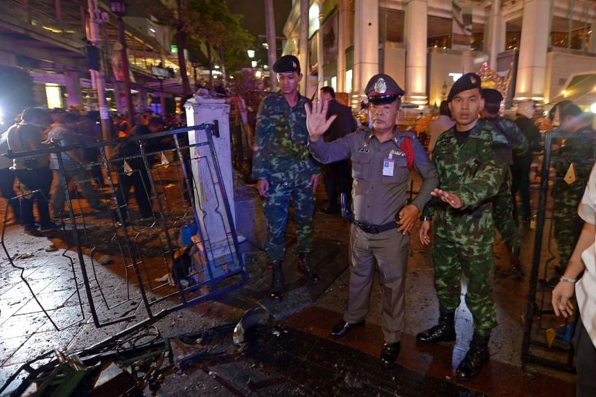 Thai soldiers and police stand guard after a bomb exploded outside a religious shrine in central Bangkok late on Aug 17.