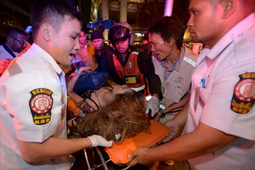 Thai rescue workers transport an injured person after a bomb exploded outside a religious shrine in central Bangkok late on Aug 17.