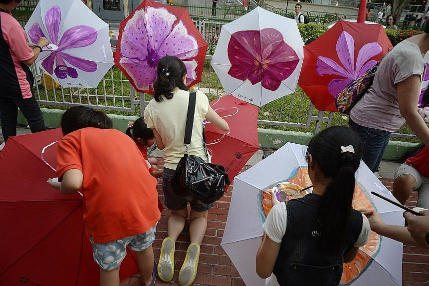 Marine Parade residents painting on umbrellas at the PAssionArts Festival held at Marine Parade Promenade yesterday. The PAssionArts Village @ Arts D'Marquee celebrated the heritage of the nearby Joo Chiat and Katong areas and welcomed crowds of abou