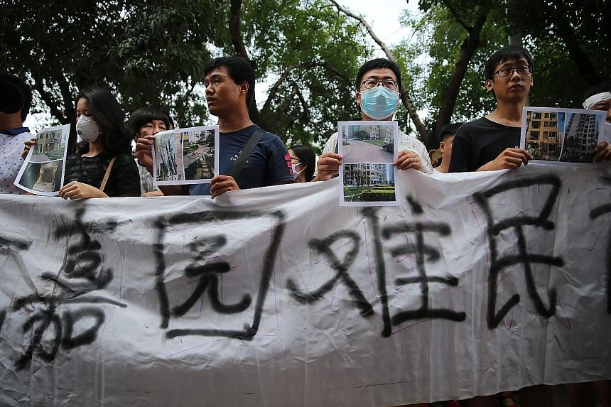 Residents of a block affected by the Tianjin explosions last week holding photos of damaged homes at a rallyin the northern Chinese city yesterday.
