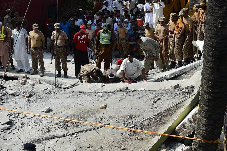 Pakistani troops and rescuers searching for survivors of yesterday's blast, which took place at the home of Mr Shuja Khanzada, home minister of Punjab province. The explosion brought down the roof of the building.