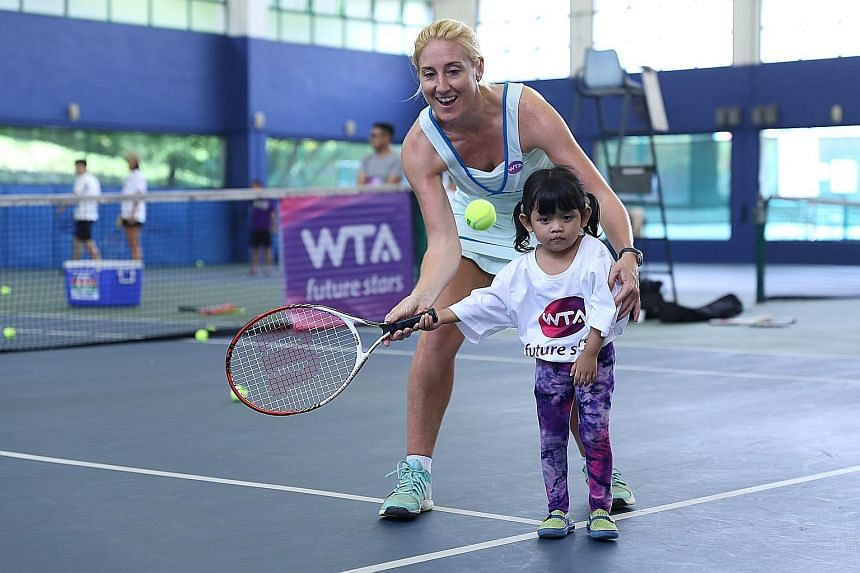 WTA Finals tournament director and vice-president for Asia-Pacific, Melissa Pine, coaching four-year-old Shazia Malika at the WTA Future Stars clinic at Keppel Club.