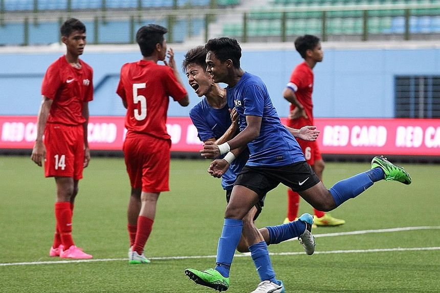 Singapore Under-16's Saifullah Akbar (in green boots) celebrating with team-mate Elliot Ng after scoring the penalty that won the match against the Singapore U-15 team in the Lion City Cup third-place play-off. Both teams' performances came under cri