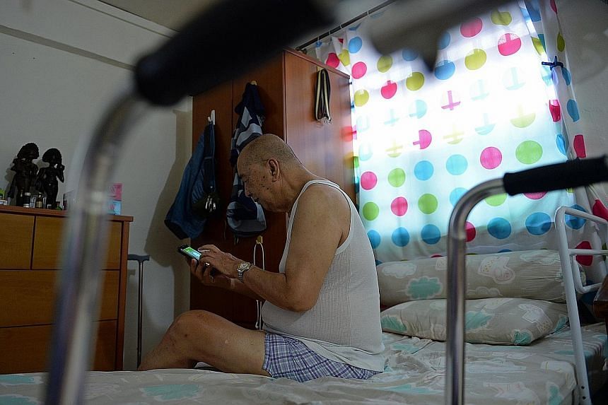 Mr Tan Ngian Wee, 80, calling friends to let them know he has reached home safely. He rarely leaves his one-room rental flat in Chin Swee Road, except for visits to the nearby Hua Mei centre for physiotherapy and other programmes.