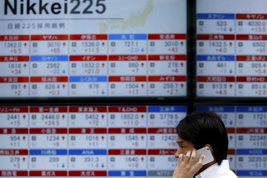 A pedestrian using his mobile phone walks past electronic boards showing the stock prices outside a brokerage in Tokyo, Japan on Aug 17, 2015.