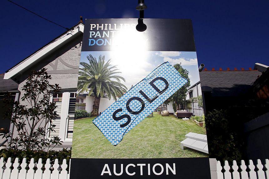 A sign stands at the front of a house after it was sold at an auction in the Sydney suburb of Waverley in Australia.