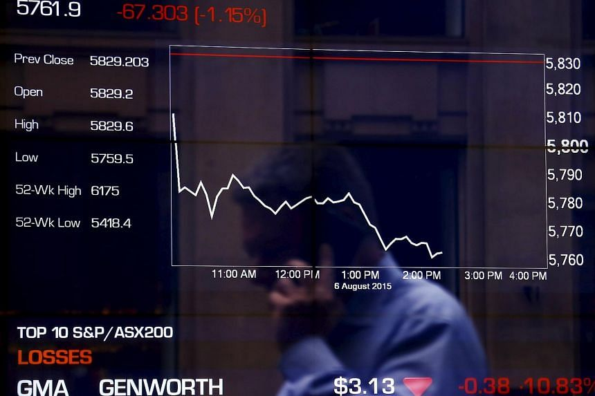 A pedestrian is reflected in a window as he talks on a phone walking past boards displaying stock prices at the Australian Securities Exchange in central Sydney, Australia, on Aug 6, 2015.