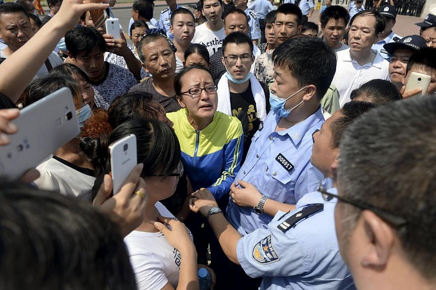 A woman speaks to a government official (bottom right), near policemen during a protest to demand information about those missing following Wednesday's blasts, mostly firefighters, in front of the Binhai new district government building, in Tianjin o