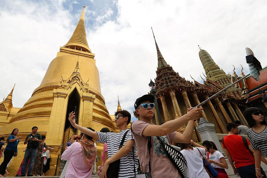 Tourists taking selfies at the Emerald Buddha Temple in Bangkok on Aug 7.