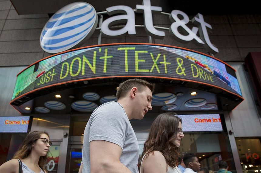 People walking past the AT&T store in New York's Times Square on June 17. AT&T stand accused of assisting the NSA to spy on Internet users.