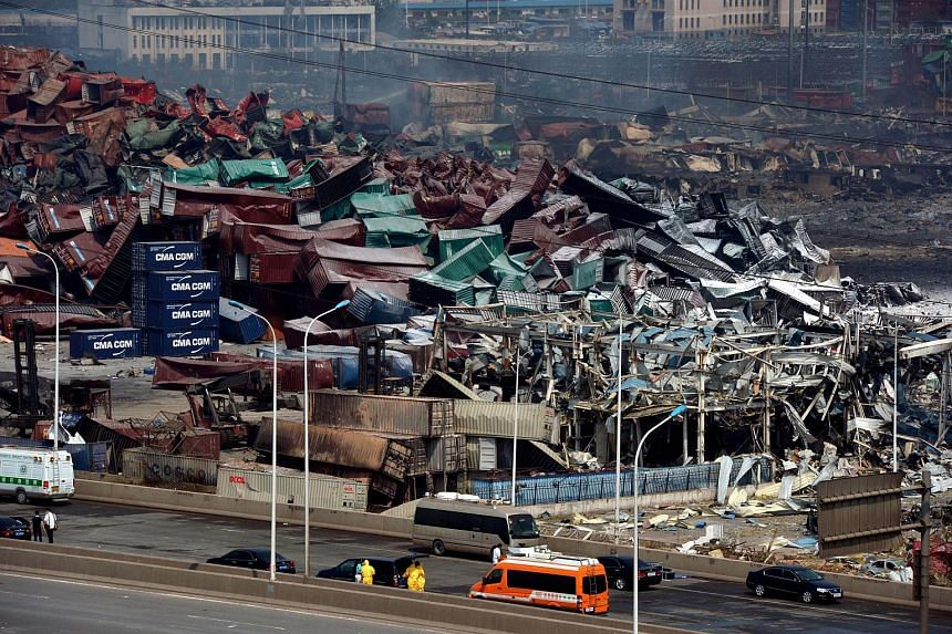 This photo taken on Aug 16, 2015 shows rescuers (foreground) working as mangled cargo containers and wreckage are seen at the site of the explosions in Tianjin.