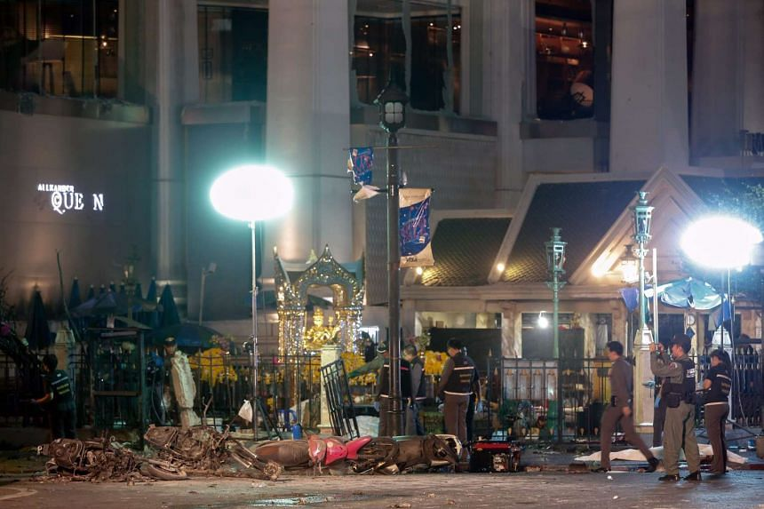 Motorcycles lie among the wreckage of a bomb blast as forensic police inspect the scene near Erawan Shrine, central Bangkok, Thailand on Aug 17.