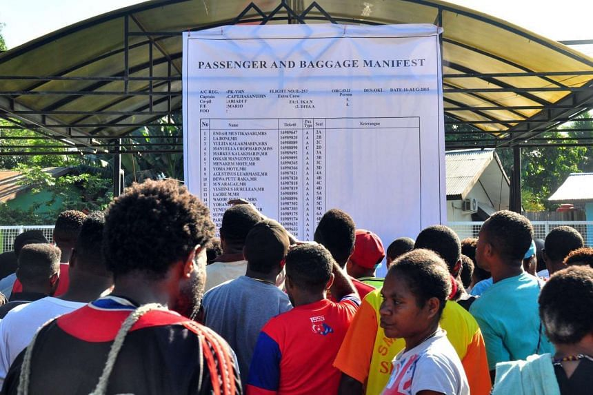Relatives of passengers onboard the missing Trigana Air plane read the passenger manifest at Sentani airport near Jayapura, Indonesia, on Aug 17, 2015.