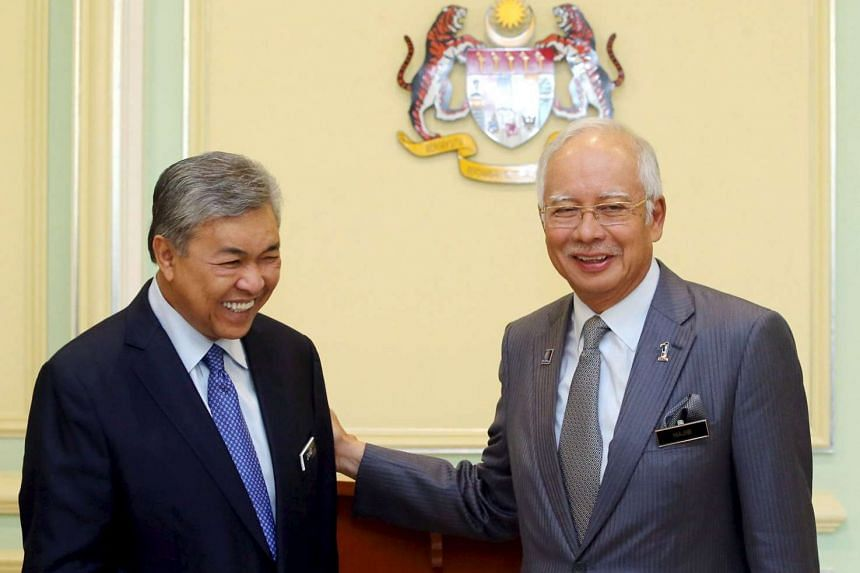 Malaysian Prime Minister Najib Razak (right) announcing the appointment of new Deputy Prime Minister Ahmad Zahid Hamidi (left) following a Cabinet reshuffle in Putrajaya, on July 28, 2015.