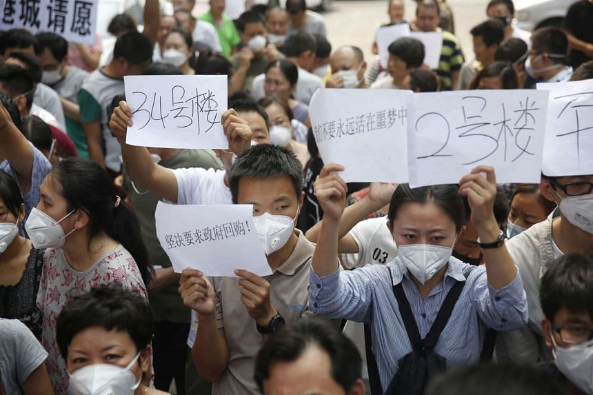 Residents, whose homes were destroyed in the explosion at a chemical warehouse last week, protest outside the hotel where authorities are holding a press conference in Tianjin on Aug 17, 2015.