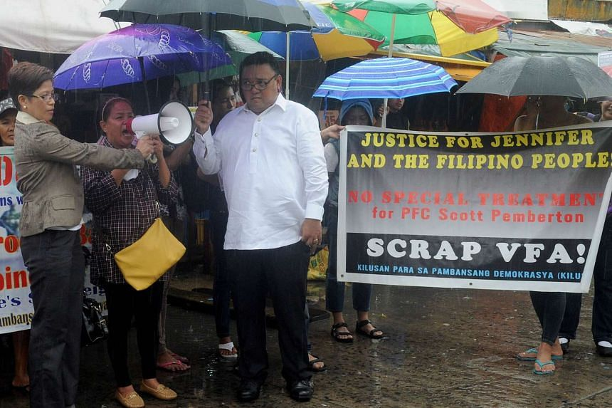 The mother of murder victim Jennifer Laude, Julita Cabillan (centre), flanked by lawyers Virgie Suarez (left) and Harry Roque (right), joins protesters outside the Hall of Justice in the Philippine city of Olongapo on Aug 10, 2015.