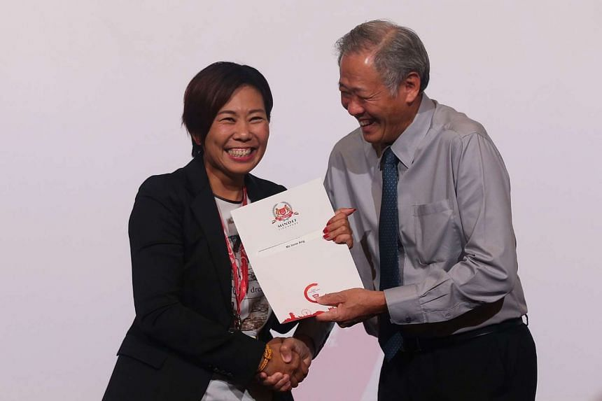 Minister for Defence Dr Ng Eng Hen (right) presents a certificate of appointment to Ms Irene Ang (left), who volunteers with the SAF Music and Drama Company's artistic advisory board.