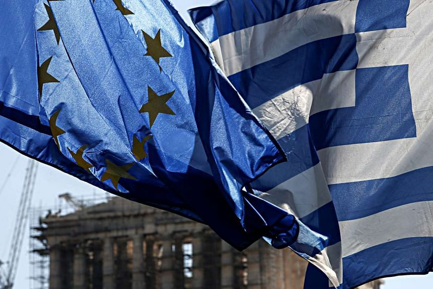 A EU flag (left) flies beside a Greek national flag in front of the Parthenon temple on Acropolis Hill in Athens, Greece.