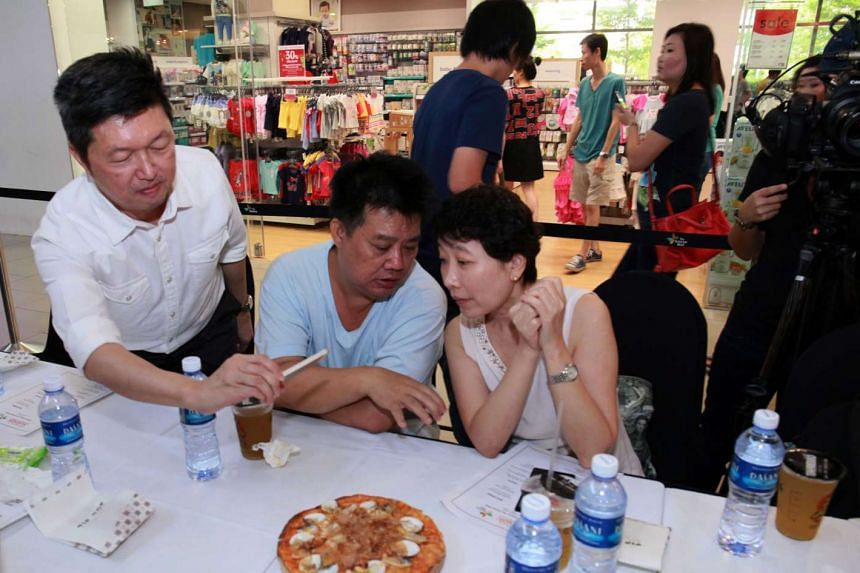 Mr Wong Ah Yoke (above, left) and Ms Tan Hsueh Yun mingling with contest winners at The Seletar Mall.