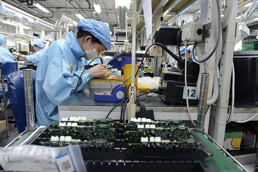 Workers at an electronics manufacturing company that makes printed circuit boards. Although exports for the important electronics sector rose 2.3 per cent last month, building on June's 7.6 per cent expansion, this was offset by a 2.1 per cent fall i