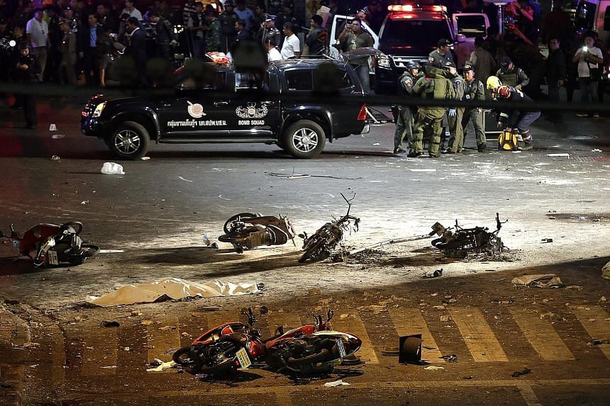 Investigators (above) at the Erawan Shrine, where blast victims were covered with white cloth. A bomb squad (below, right) investigated the nearby scene, where charred motorcycles lay on the street. Rescue workers attending to an injured person after