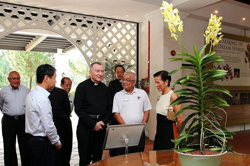 Left: Cardinal Parolin (centre) viewing the Aranda Lee Kuan Yew during a tour of the Botanic Gardens yesterday. Accompanying him were Singapore's Ambassador to the Holy See Barry Desker (far left), NParks chief executive Kenneth Er (second from left)