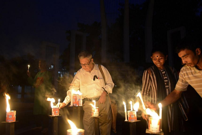"Ajoy Roy (left), the father of slain Bangladeshi blogger Avijit Roy, takes part in a candlelight vigil to protest the spate of blogger killings. Police have arrested a British citizen they believe was the ""main planner"" of the murders of bloggers Avi"