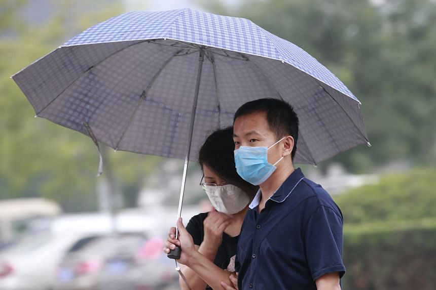 A couple takes shelter from the rain under an umbrella at Binhai new district in Tianjin, China on Aug 18, 2015.