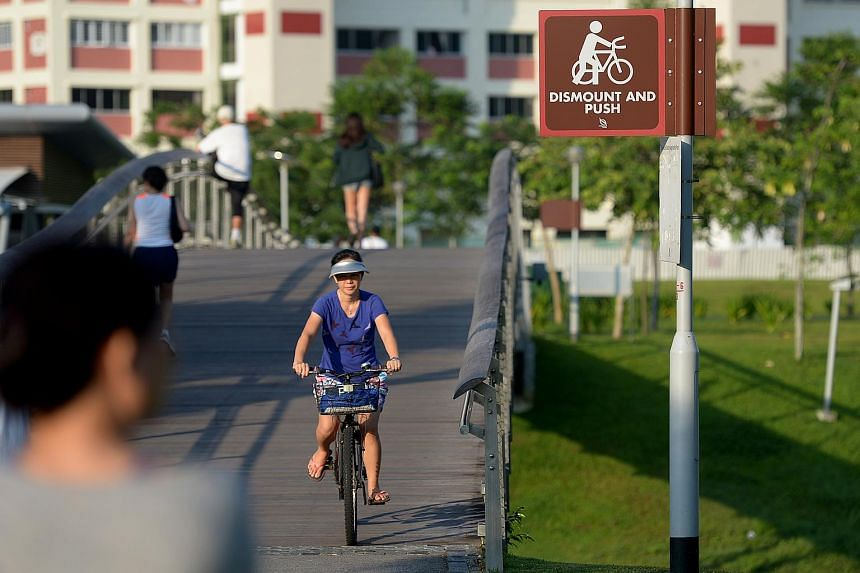 A woman riding her bicycle on a bridge at Bishan Park.