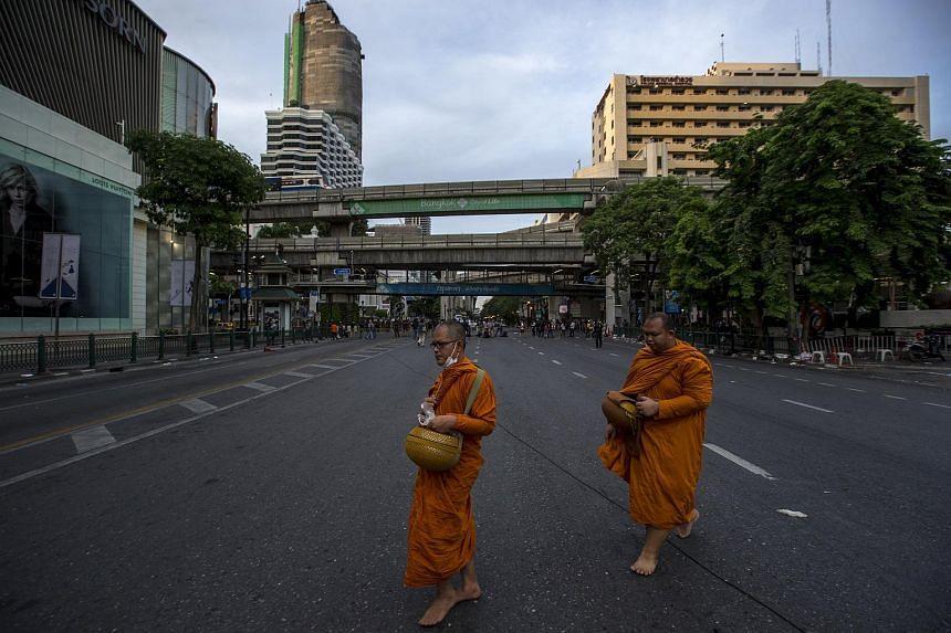 Thai Buddhist monks walk past near the scene of a blast in central Bangkok Aug 18, 2015.