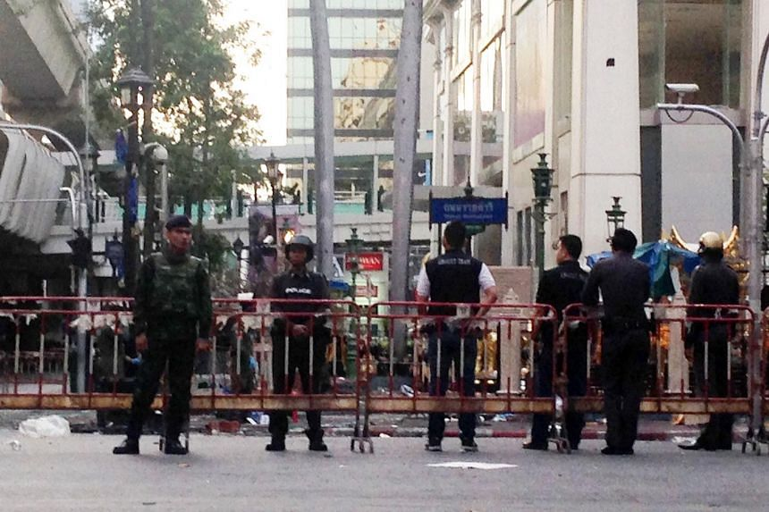 Police and soldiers stand near the damaged religious shrine in central Bangkok late on Aug 18, 2015.