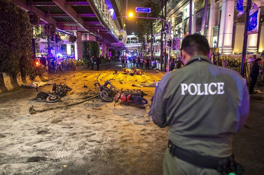 Bodies of victims are covered with white sheets among motorcycle wreckage and other debris as security forces and emergency workers gather at the scene of the blast in central Bangkok on Aug 17.