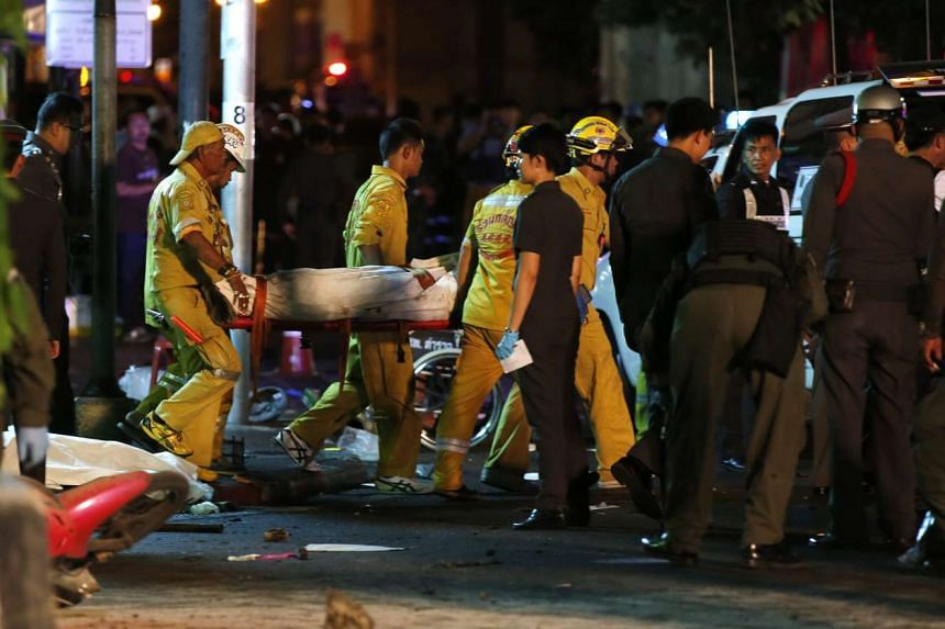Thai rescue workers carrying the covered body of a bomb victim in the aftermath of the explosion in Bangkok.