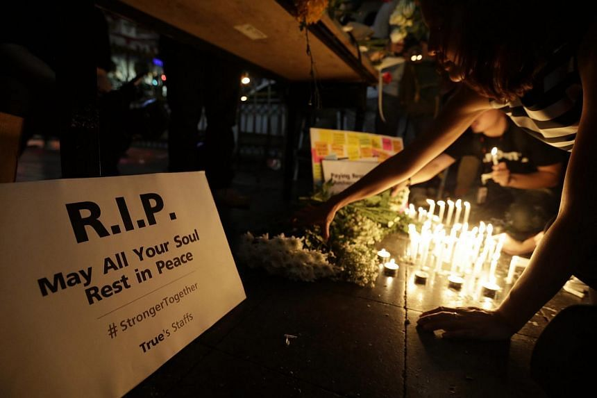Thais offer candles and flowers in central Bangkok, Thailand on Aug 18, 2015, for the victims of bombing.