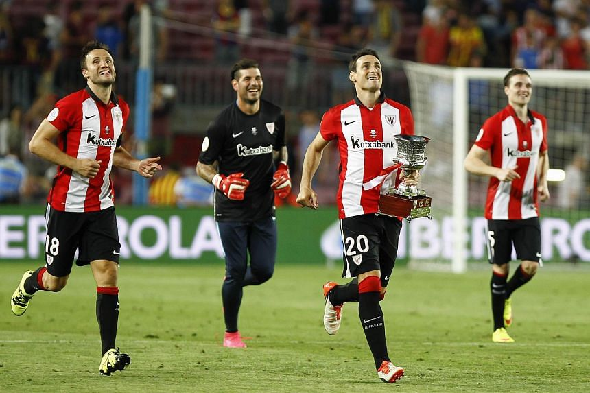 Athletic Bilbao's forward Aritz Aduriz (2nd right) runs with the Super Cup trophy next to Athletic Bilbao's midfielder Carlos Gurpegui (left) at the Camp Nou stadium in Barcelona on Aug 17, 2015.