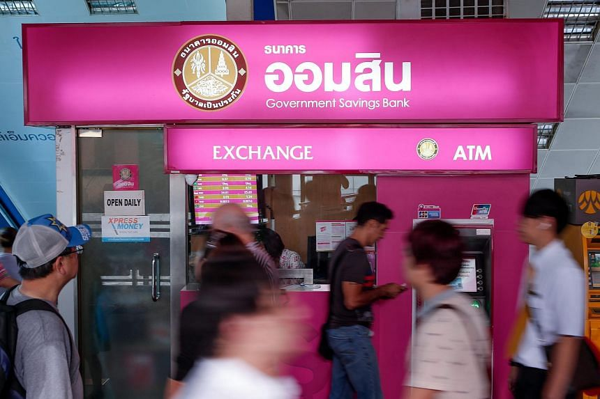 People walking past a moneychanger in Bangkok on Aug 13.