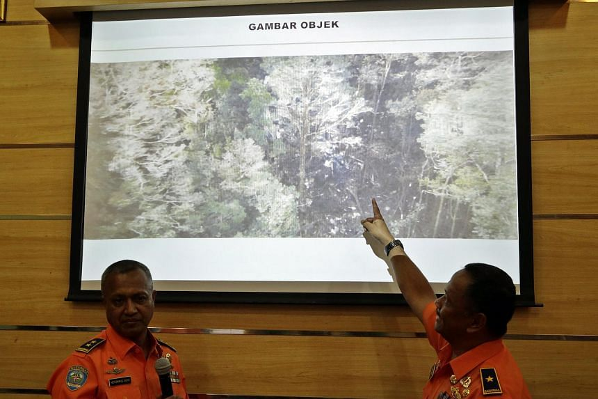 Heronimus Guru (left) and Director of Operational and Training Ivan Ahmad Rizki show a picture of the suspected crash site of a Trigana Air ATR 42 plane shortly after a press conference in Jakarta, Indonesia on Aug 17, 2015.