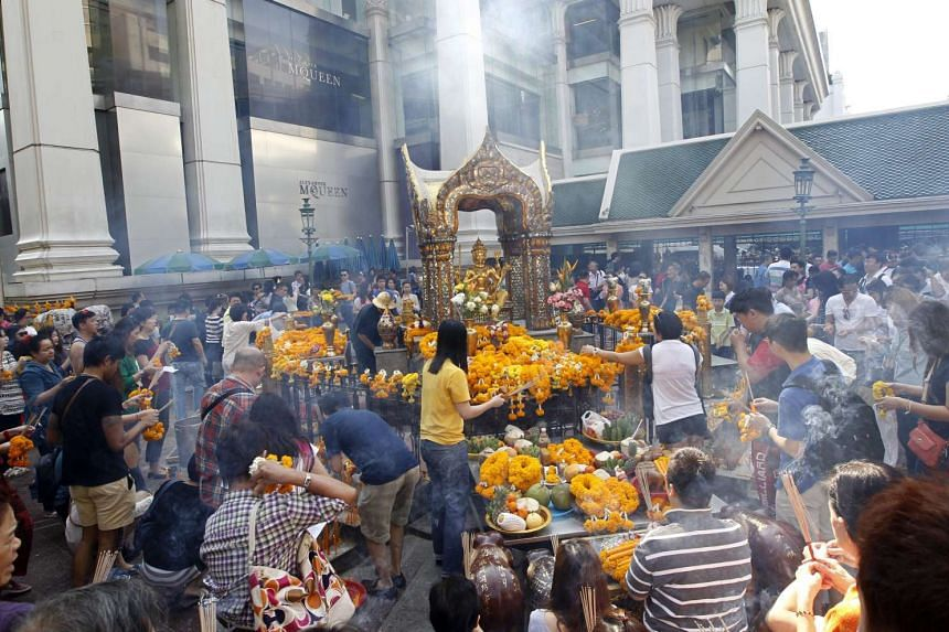 Tourists gathering to worship Hindu Creation God Brahma as merit making to mark 2015 New Year celebrations at the Erawan Shrine in 