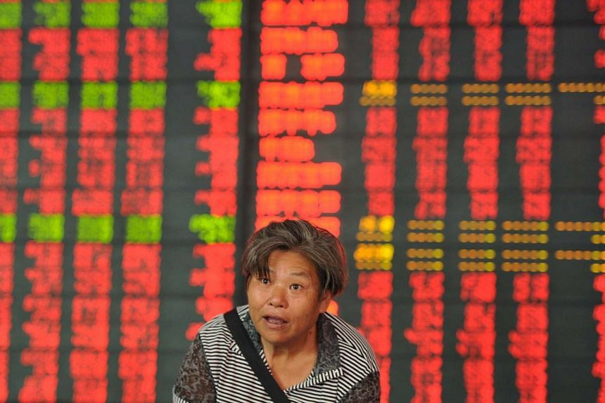 An investor reacts as she stands in front of an electronic board showing stock information at a brokerage house in Fuyang, Anhui province, China, on Aug 7, 2015.