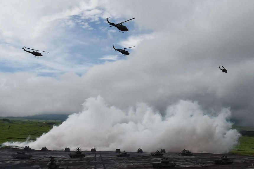 Tanks and helicopters from Japan's Ground Self-Defense Force participate in an annual live fire exercise at the foot of Mount Fuji on Aug 18, 2015.