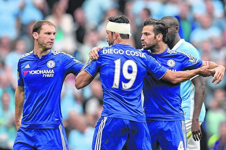 Defender Branislav Ivanovic (left) and midfielder Cesc Fabregas restrain striker Diego Costa (2nd left) as they leave the pitch at half time during the EPL football match between Manchester City and Chelsea at The Etihad stadium in Manchester.