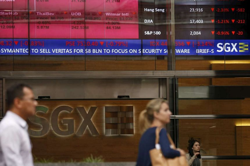 People pass a stock board showing stocks in red outside the Singapore Exchange in the central business district in Singapore on Aug 12, 2015.