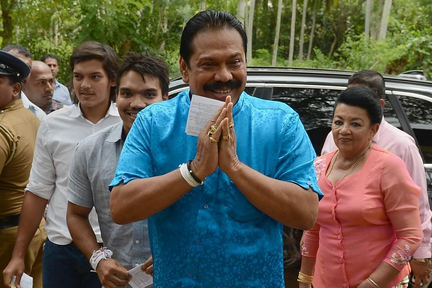 Former Sri Lankan president and parliamentary candidate Mahinda Rajapakse (centre) gestures on his arrival with his family to cast his vote at a polling station in his native town of Tangalla on Aug 17, 2015.