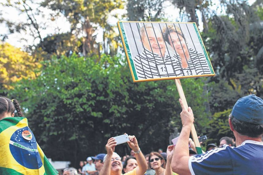 A demonstrator with a placard featuring Brazilian President Dilma Rousseff and her predecessor Luiz Inacio Lula da Silva in Sao Paulo on Sunday. Protests across Brazil have kept the pressure on Ms Rousseff, who is grappling with a colossal bribery sc