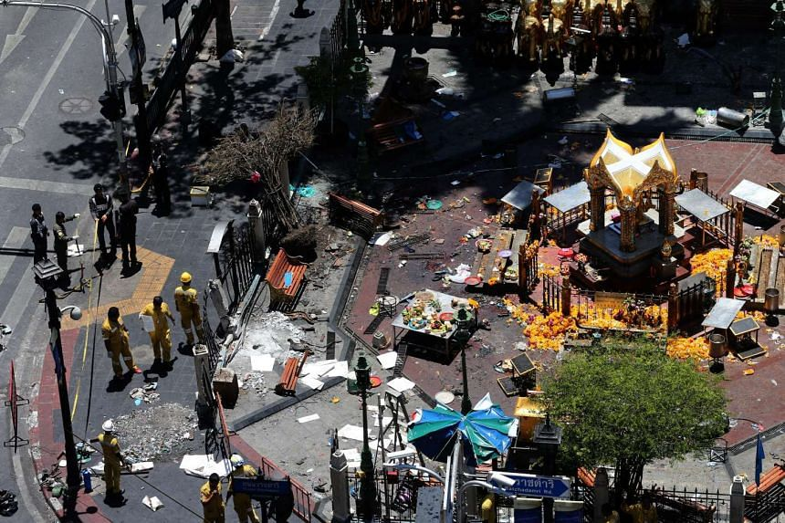 Thai police officers and emergency staff inspecting the blast site at Erawan Shrine in central Bangkok where a bomb was detonated on Aug 17, 2015.