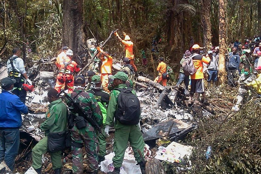 Indonesian rescuers search through the wreckage of the Trigana Air ATR 42-300 twin-turboprop plane at the crash site in the mountainous area of Ogbape, near Oksibil district located in Papua province.