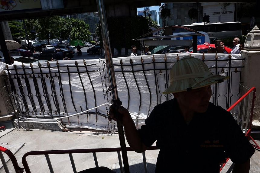 A metal fence bent from the impact of the Monday blast is seen in an area within Erawan Shrine which has been cordoned off.
