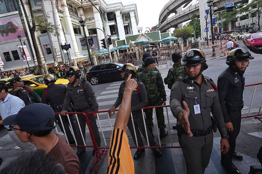 Security personnel keeping the public away yesterday at Bangkok's Erawan Shrine where a bomb went off on Monday night, killing 20 people and injuring another 120. Ms Melisa Liu and her husband Ng Su Teck had travelled to Bangkok with some companions